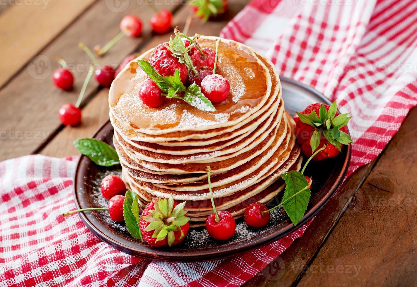 Pfannkuchen mit Beeren und Sirup im rustikalen Stil foto