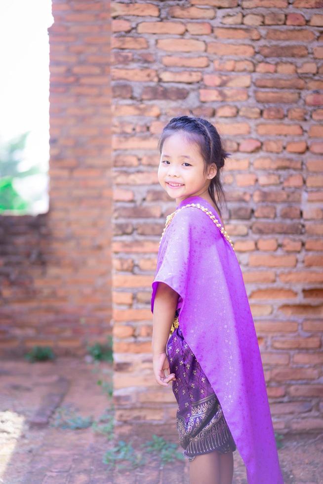 kleines asiatisches Mädchen im thailändischen Kleid foto