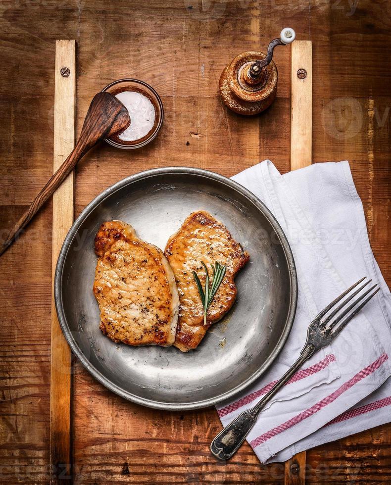 Gebratene marinierte Schweinesteaks auf rustikalem Küchentisch foto