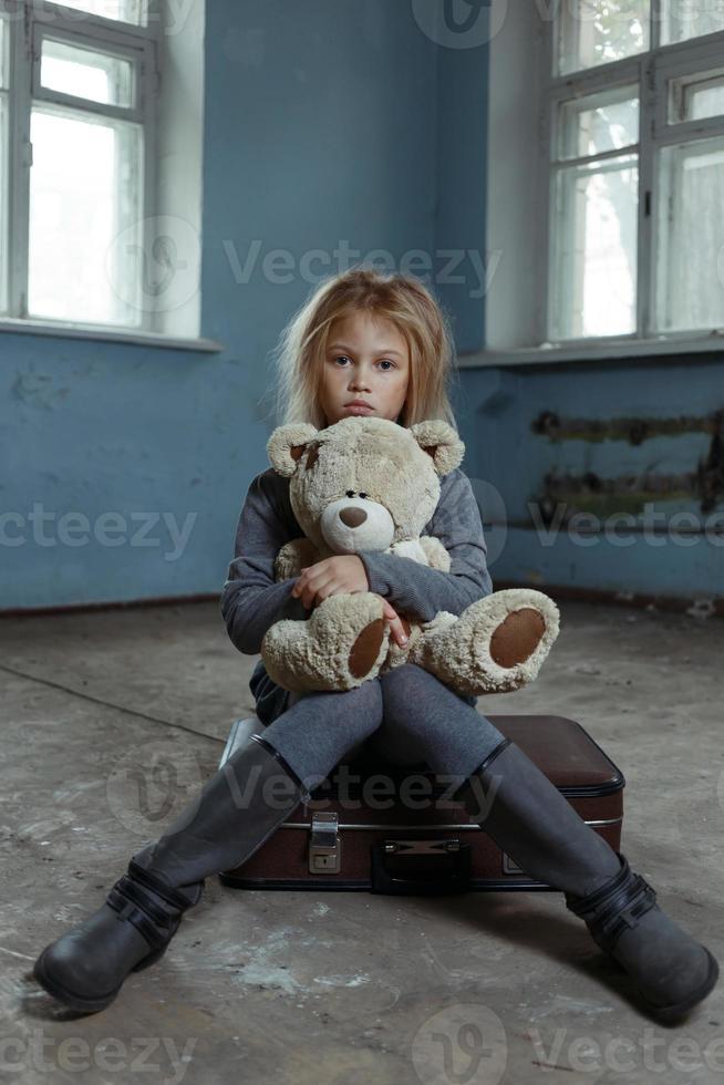 einsames Mädchen sitzt auf dem Koffer foto