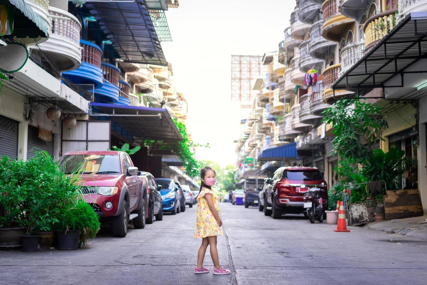 kleines asiatisches Mädchen, das eine Maske gegen Abenddämmerung und covid-19 trägt foto