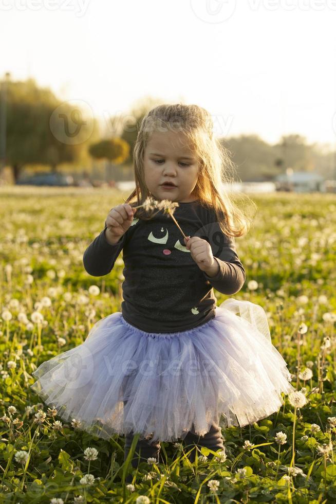 Kind, das mit Löwenzahnblume auf Gras im Feld spielt foto