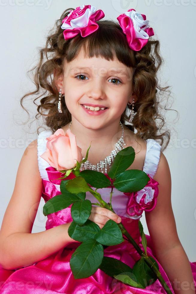 das Mädchen in einem schönen Kleid mit Rose foto
