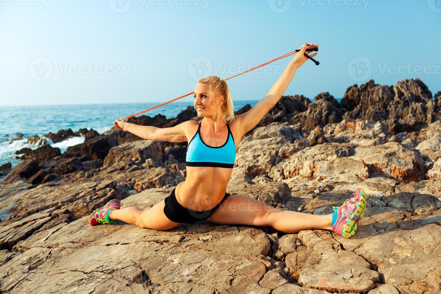 Sportlerin, die Sport auf den Felsen ausübt foto