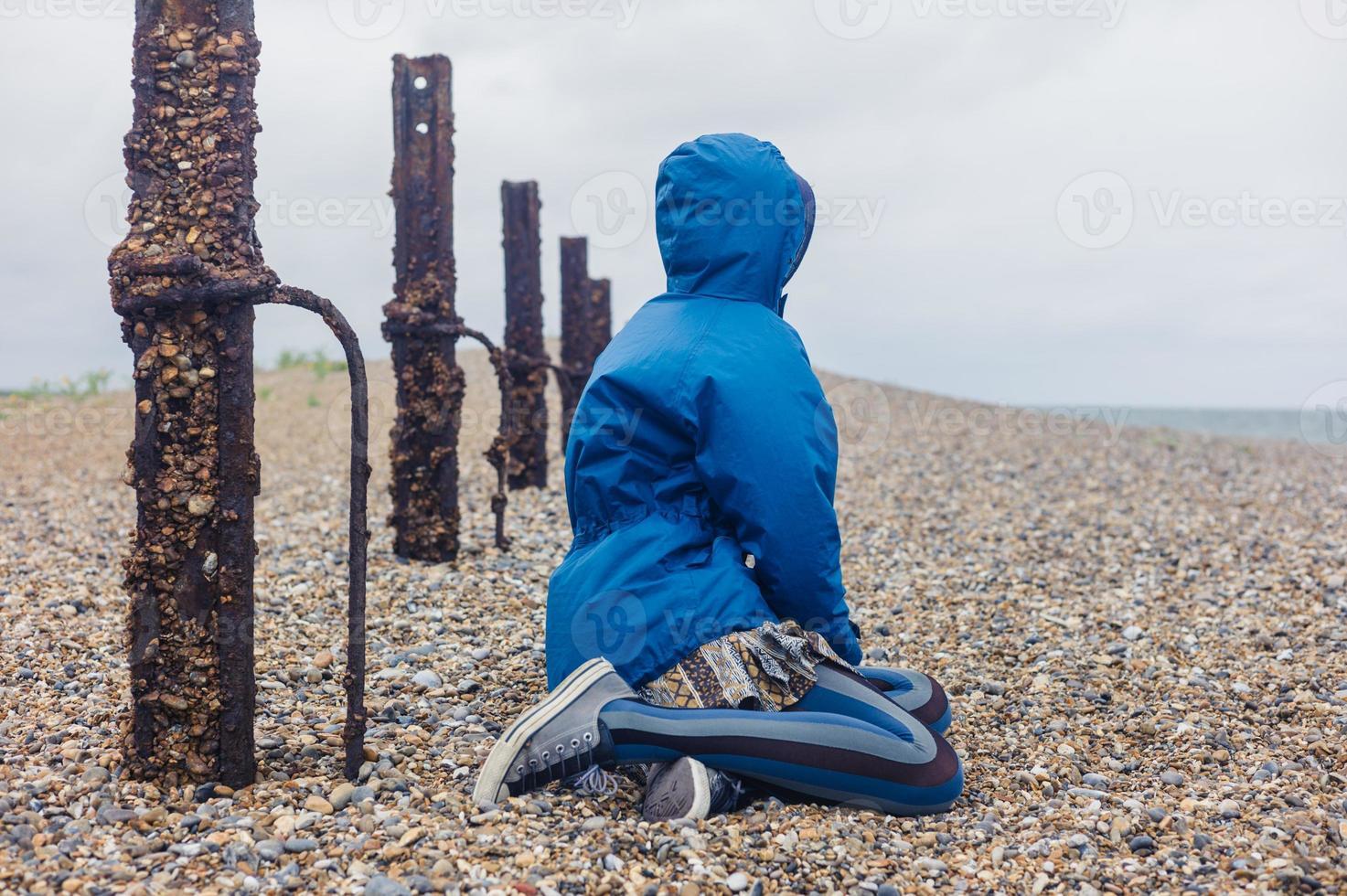junge Frau, die durch einen rostigen Zaun am Strand sitzt foto