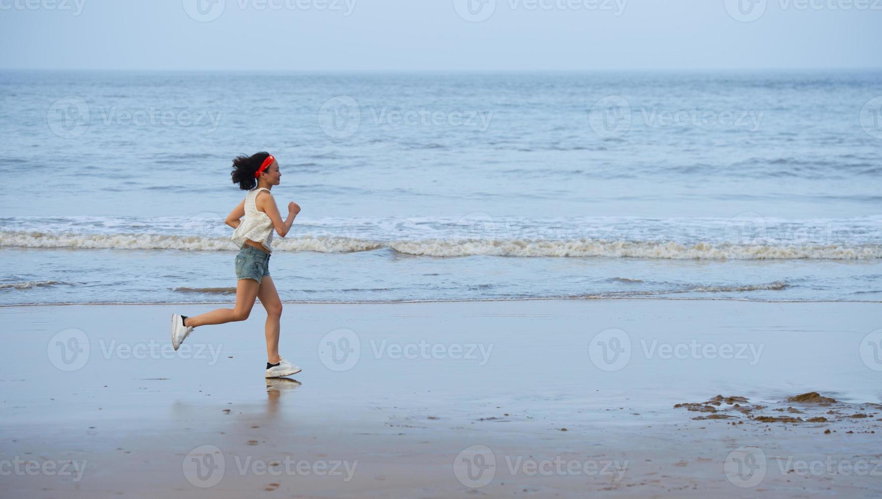 Frau läuft am Strand bei Sonnenuntergang. foto