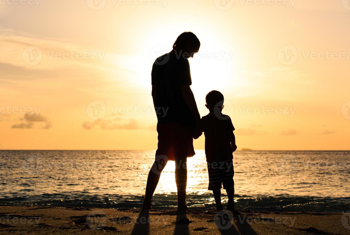 Silhouetten von Vater und Sohn, die Hände bei Sonnenuntergang halten foto