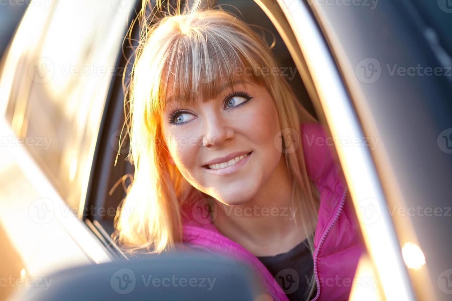 lächelndes schönes Mädchen schaut aus einem Autofenster foto