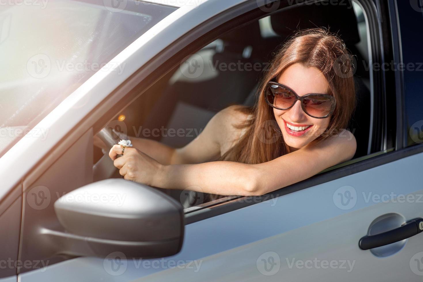 junge lächelnde Frau, die ihr neues Auto fährt foto