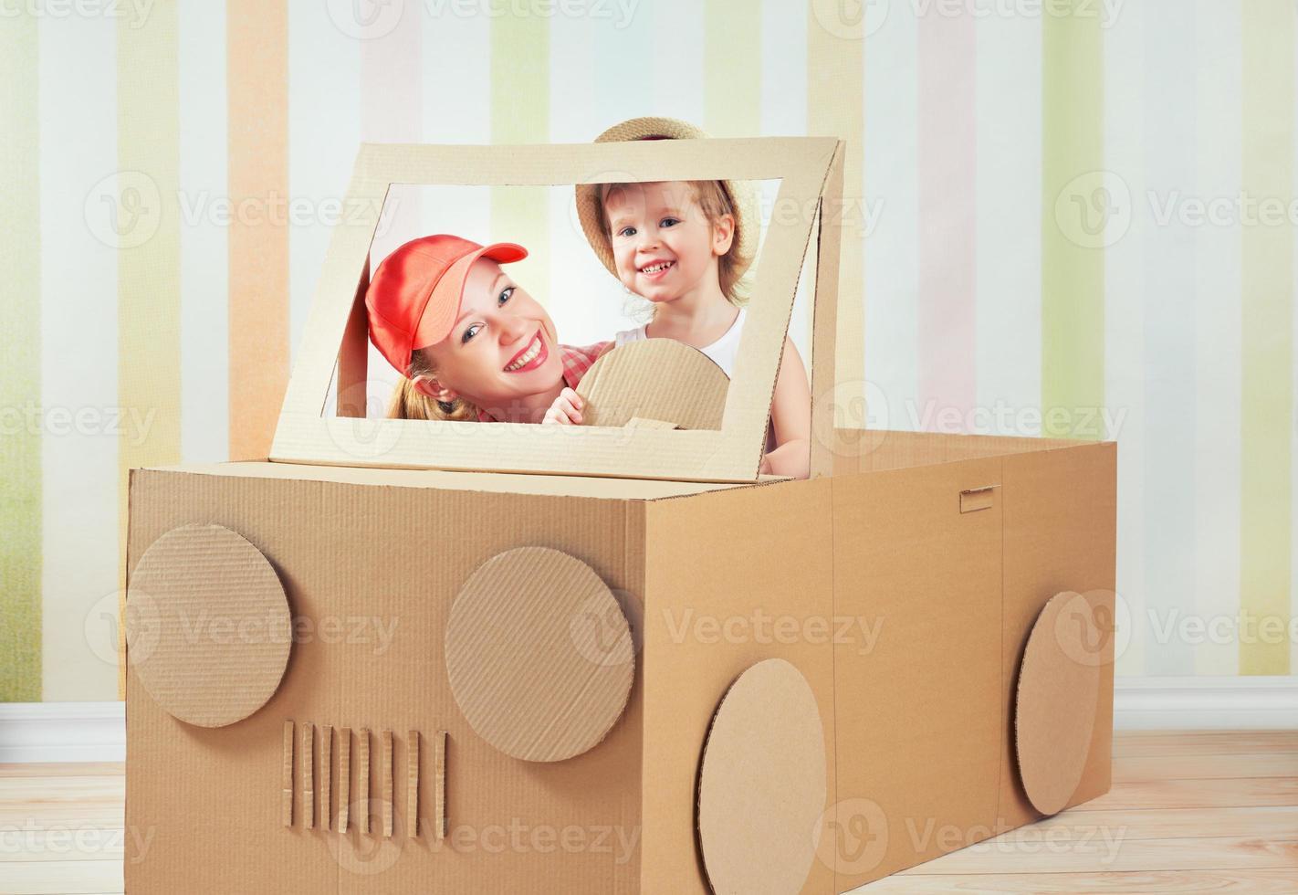 glückliche Familienmutter und kleine Tochter fahren auf Spielzeugauto foto
