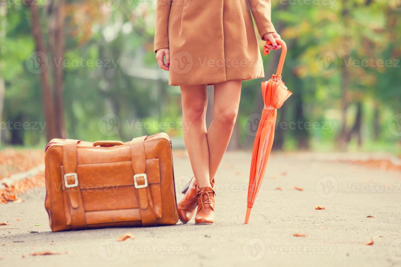 Gril im Mantel mit Regenschirm und Koffer im Park. foto