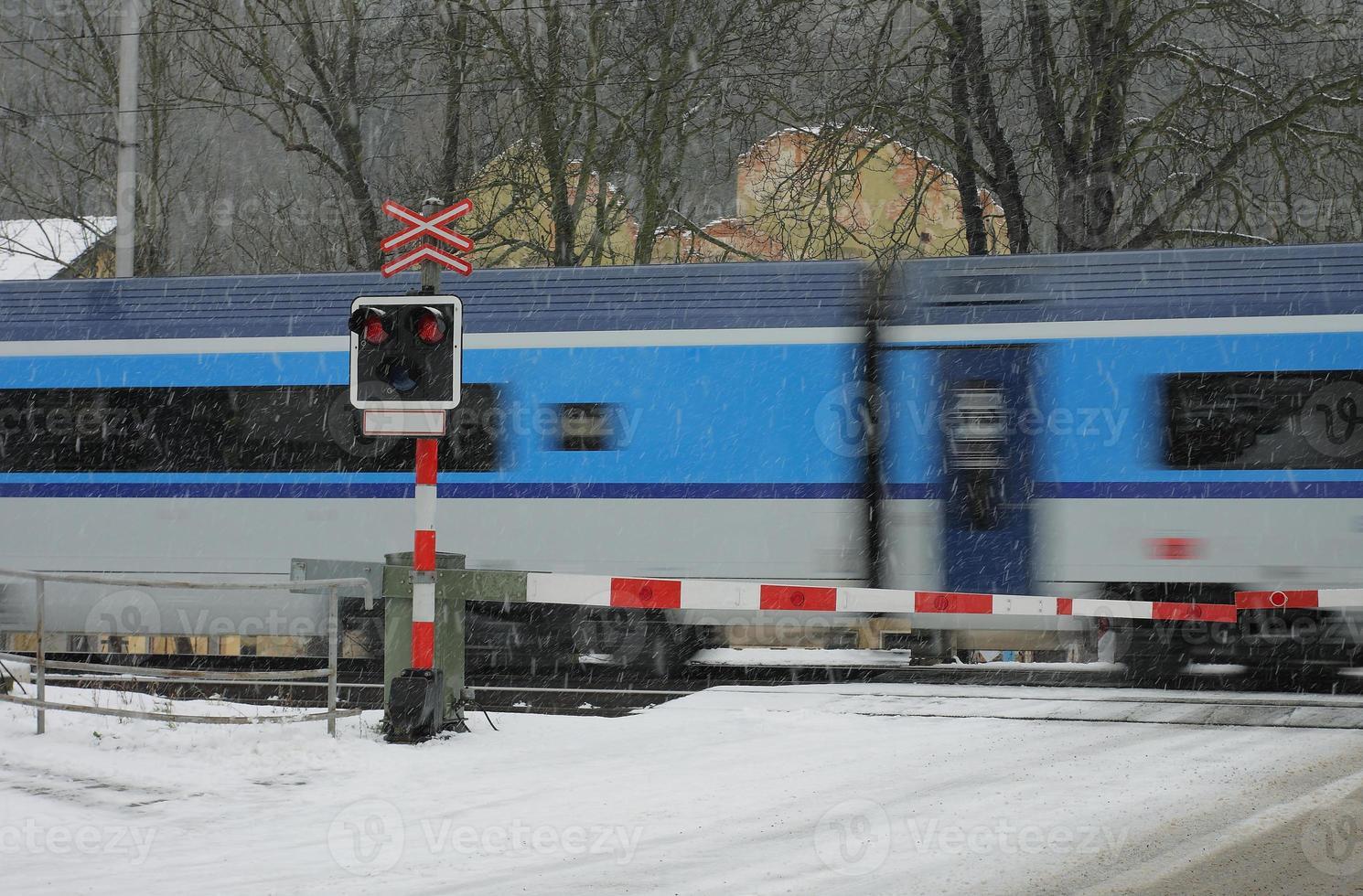 tschechischer Bahnübergang im Winter mit Zug in einem Schneesturm foto