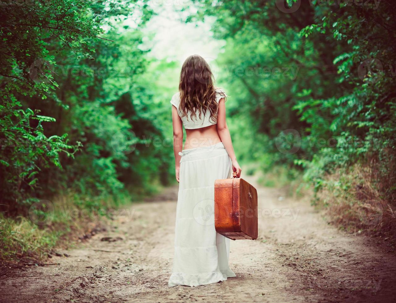 Frau mit Koffer in der Hand, die durch Landstraße weggeht foto