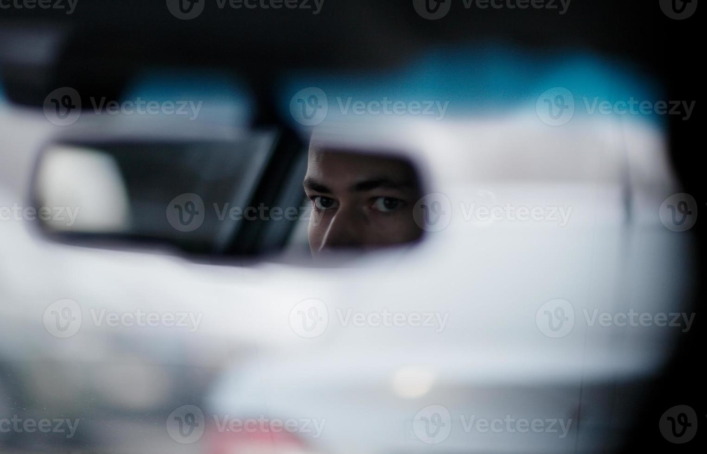 Mann, der in den Rückspiegel während der Fahrt schaut foto