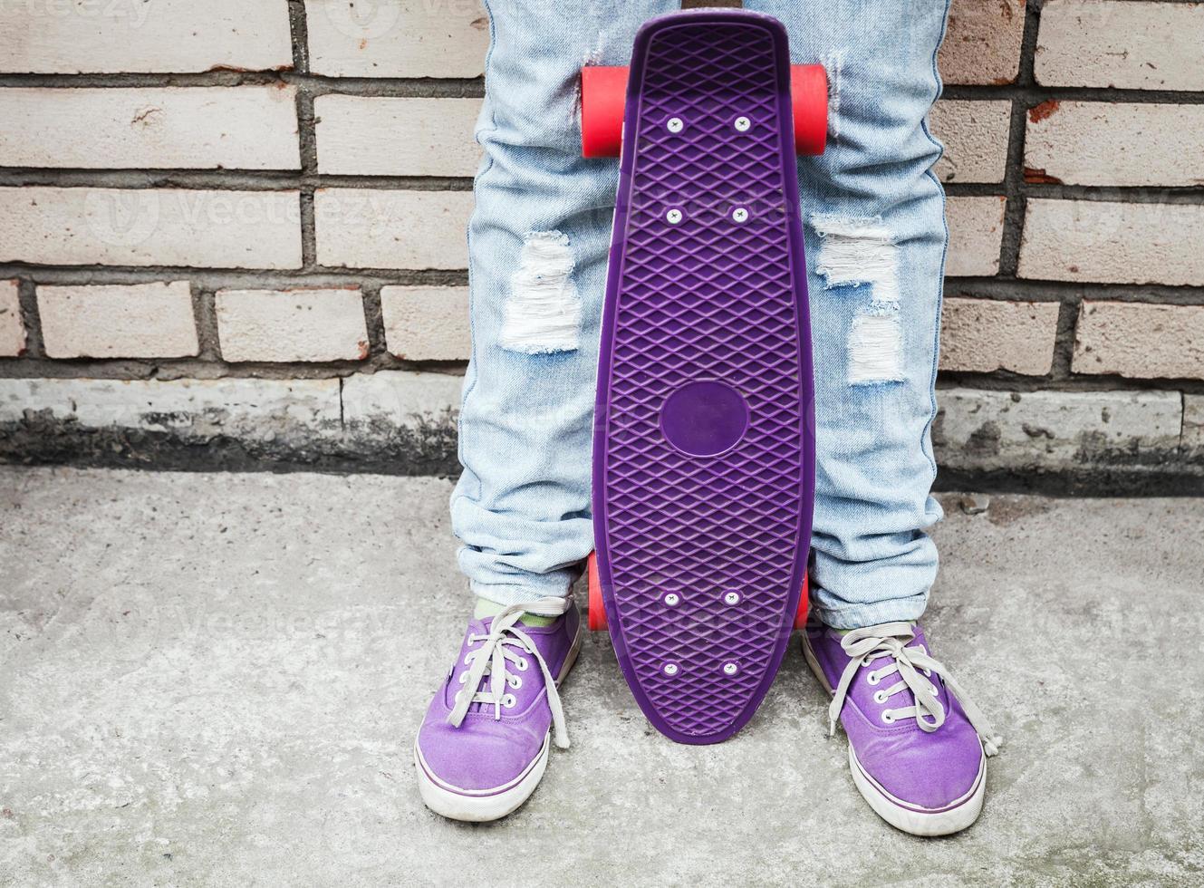 Teenager-Mädchen in Jeans hält ein Skateboard foto