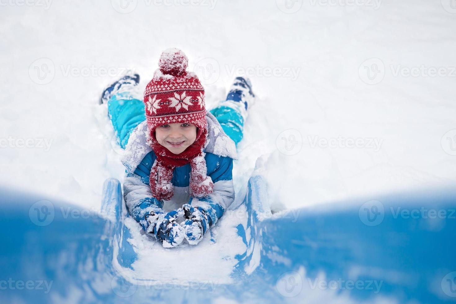 süßer kleiner Junge, der eine schneebedeckte Rutsche hinuntergeht foto