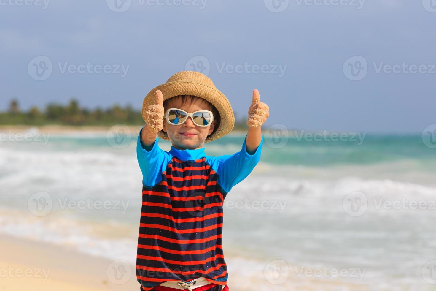 kleiner Junge Daumen hoch am Sommerstrand foto