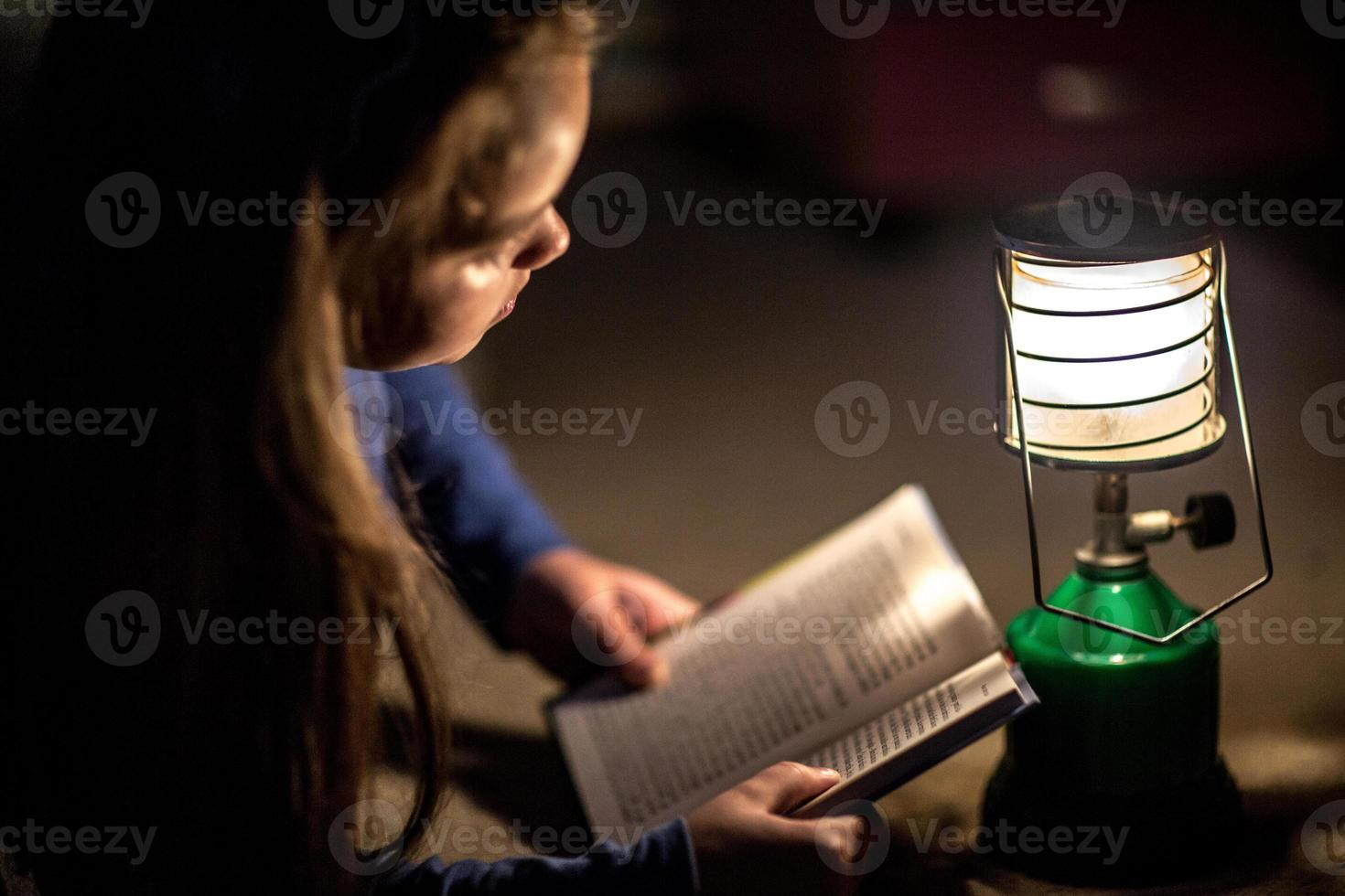 Mädchen, das Buch in der Beleuchtungslampe liest foto