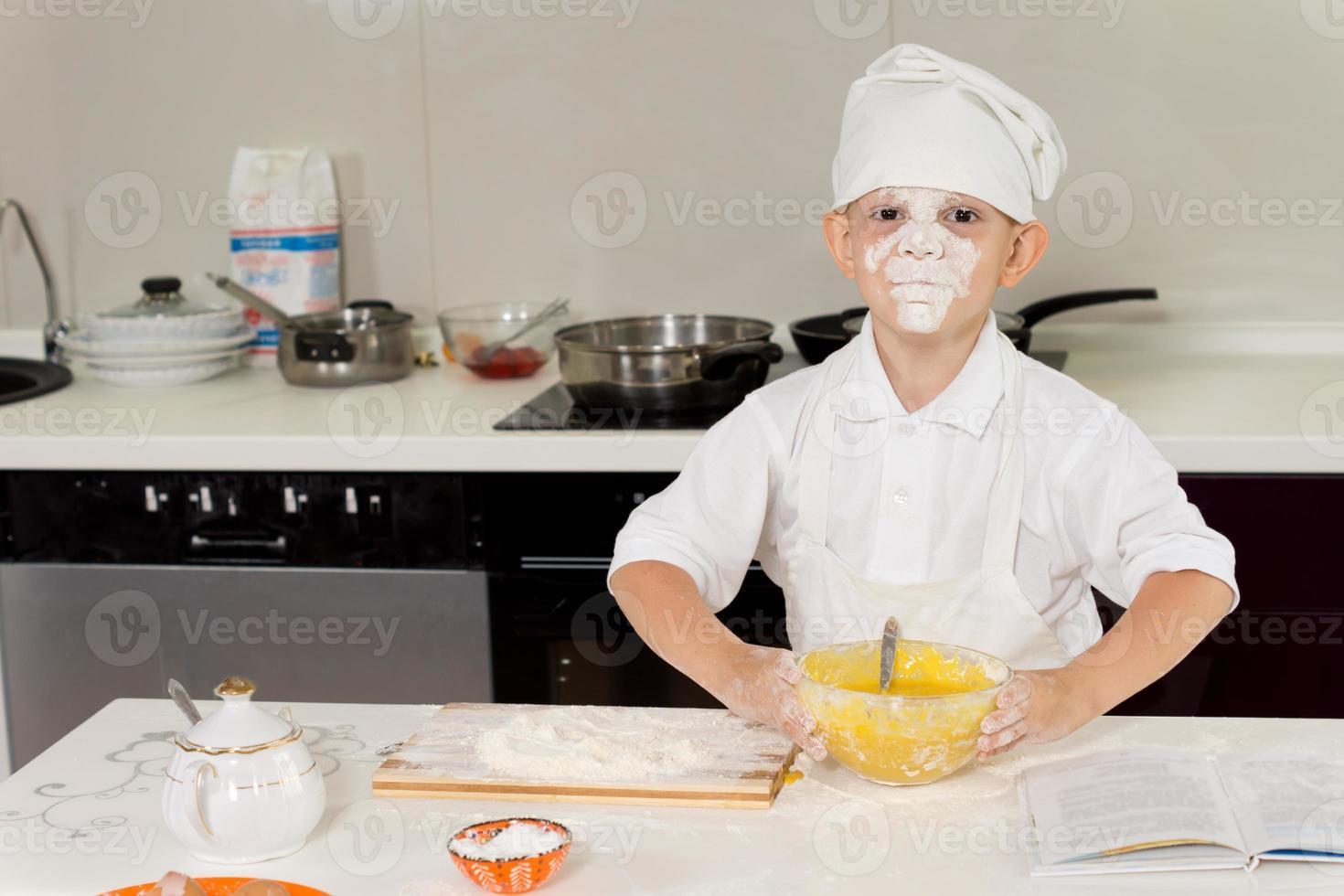 junger Koch mit Mehl im Gesicht foto