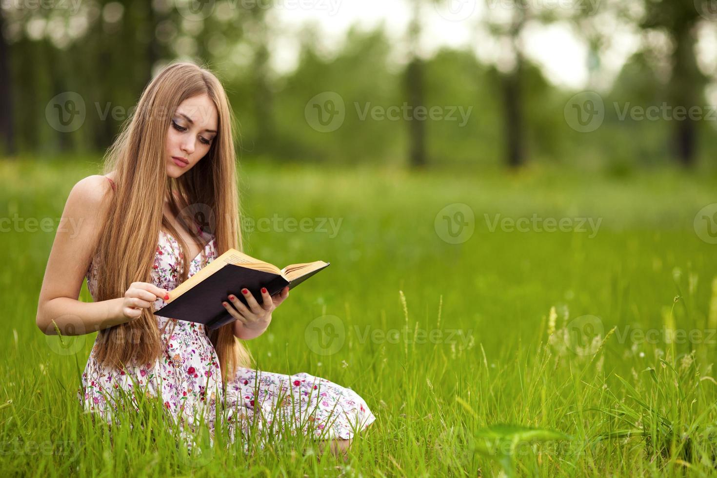 Studentin sitzt auf Rasen und liest Lehrbuch. foto
