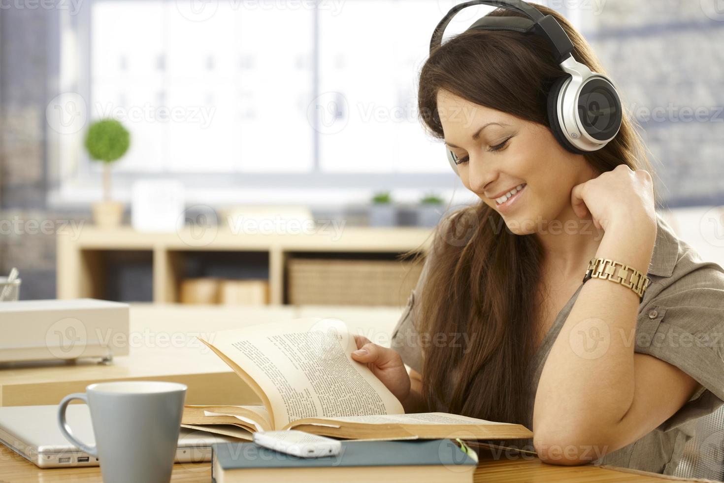 glückliche Frau mit Buch und Kopfhörern foto