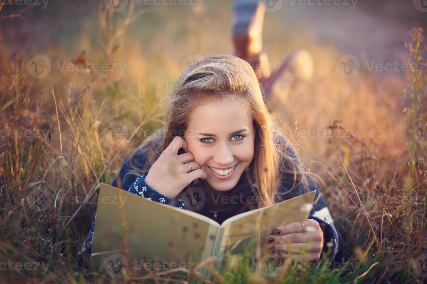schöne blaue Augenfrau, die ein Buch im Freien liest foto