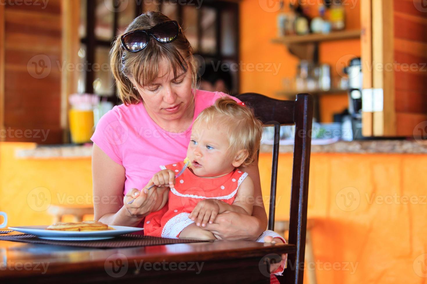 Mutter füttert kleine Tochter im Café foto
