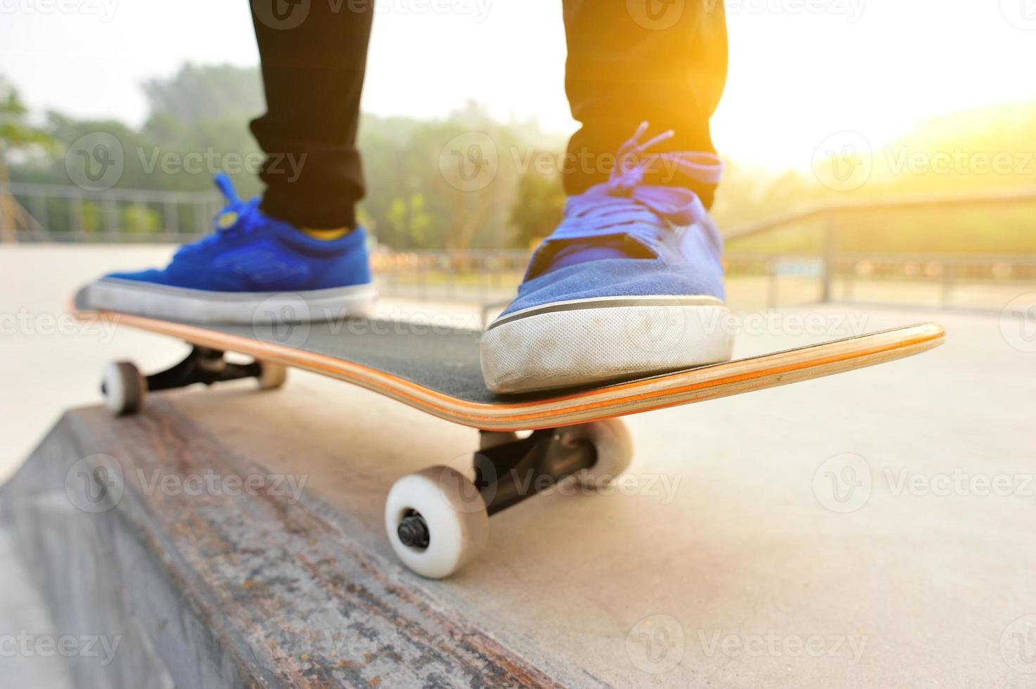 Beine in Turnschuhen auf einem Skateboard foto