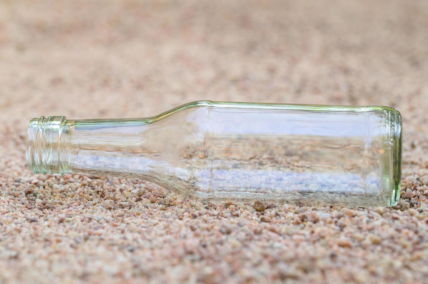 leere Glasflasche im Sand foto