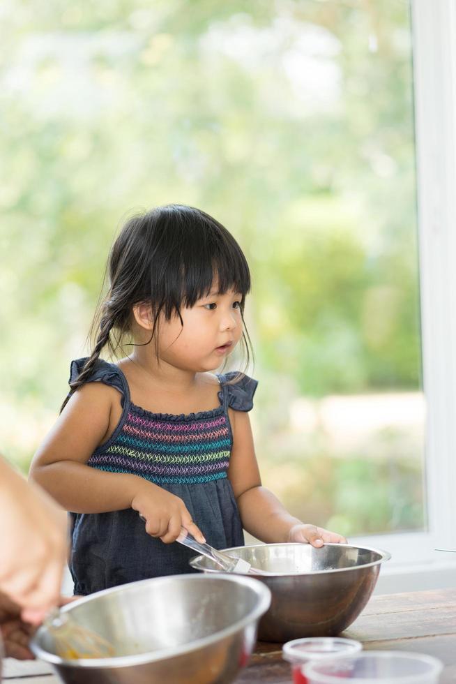 asiatisches Mädchen, das in der Küche kocht foto