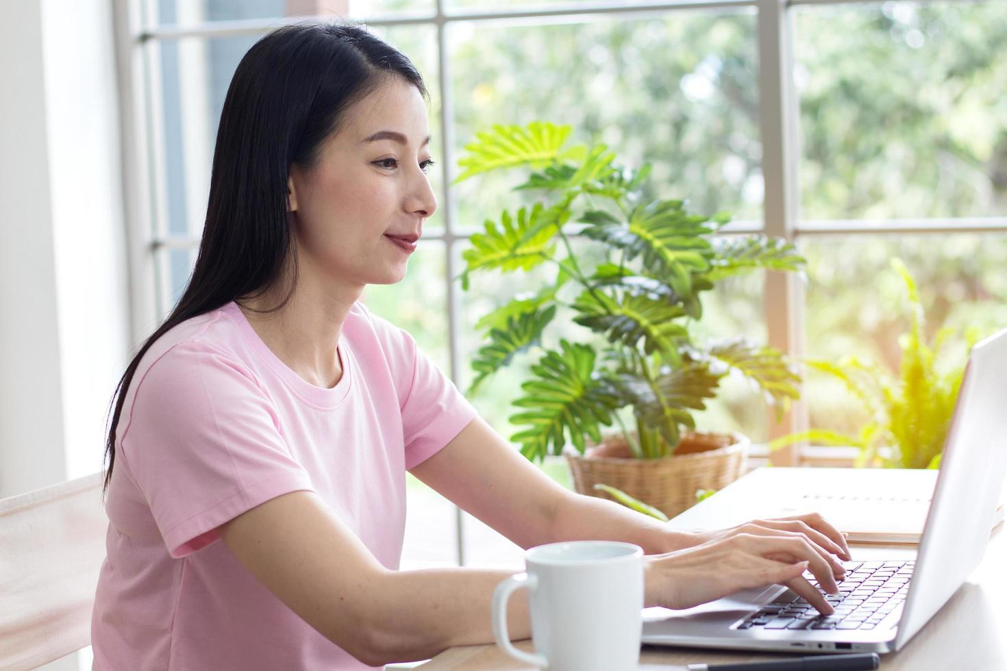 asiatische Frau, die an ihrem Laptop arbeitet foto