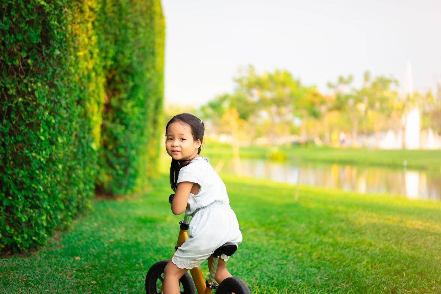 kleines Mädchen, das Laufrad im Park reitet foto