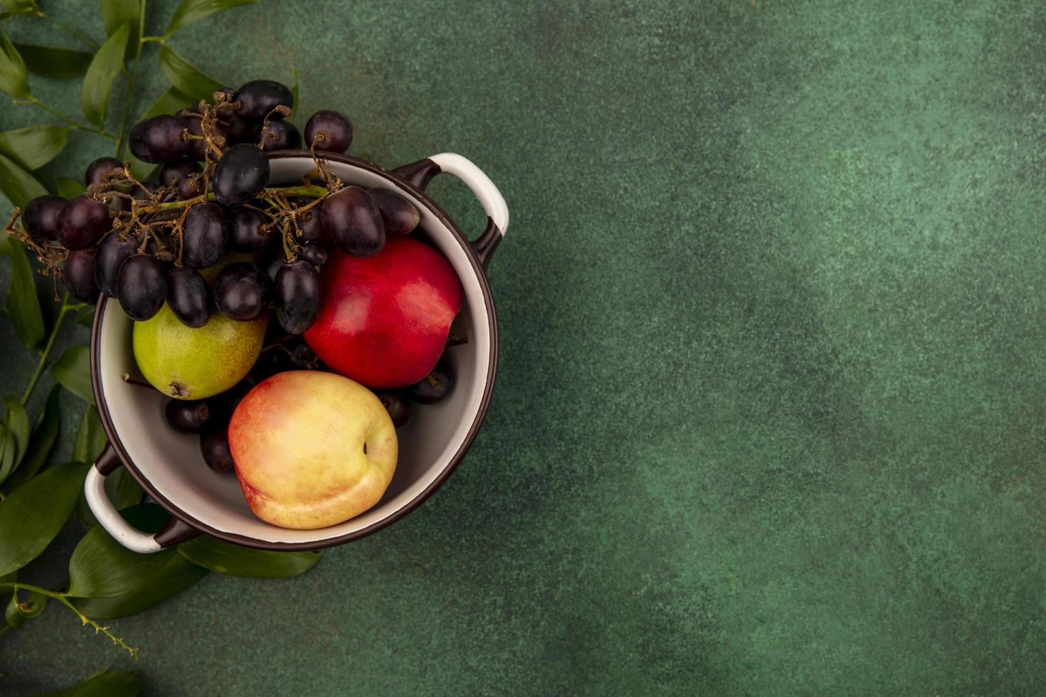 sortierte Frucht in einer Schale auf grünem Hintergrund foto