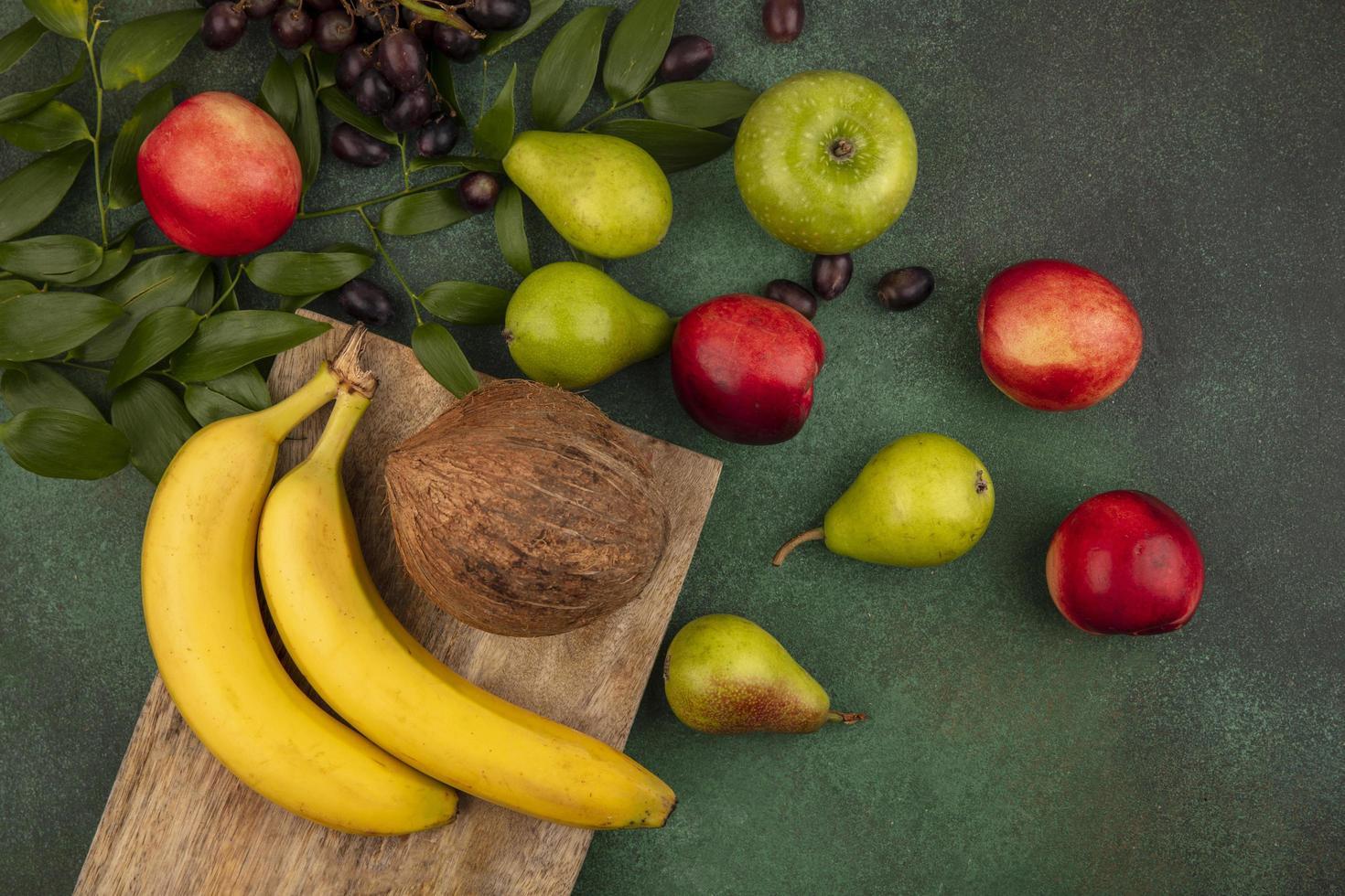 verschiedene Früchte auf Schneidebrett auf grünem Hintergrund foto