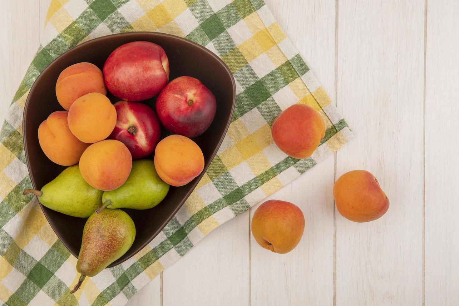 verschiedene Früchte auf neutralem Hintergrund mit kariertem Stoff foto