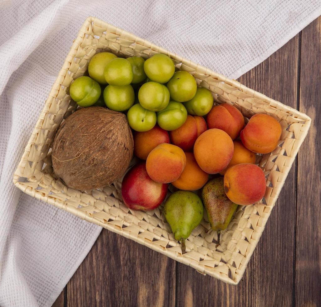 Frucht in einem Korb mit Stoff auf hölzernem Hintergrund foto