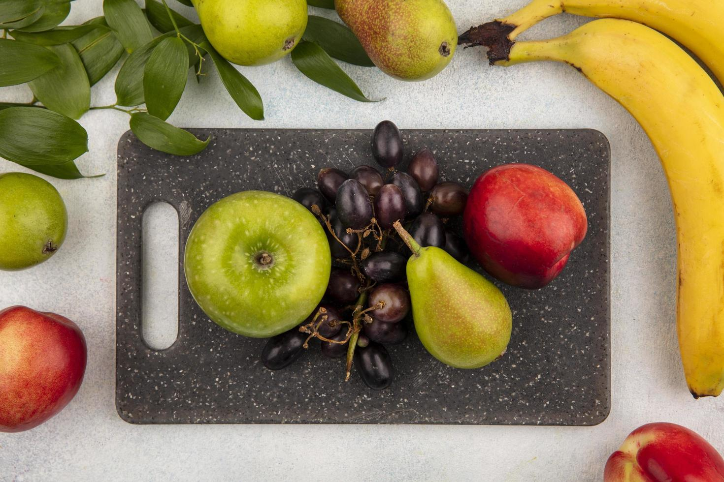 verschiedene Früchte auf Schneidebrett auf neutralem Hintergrund foto