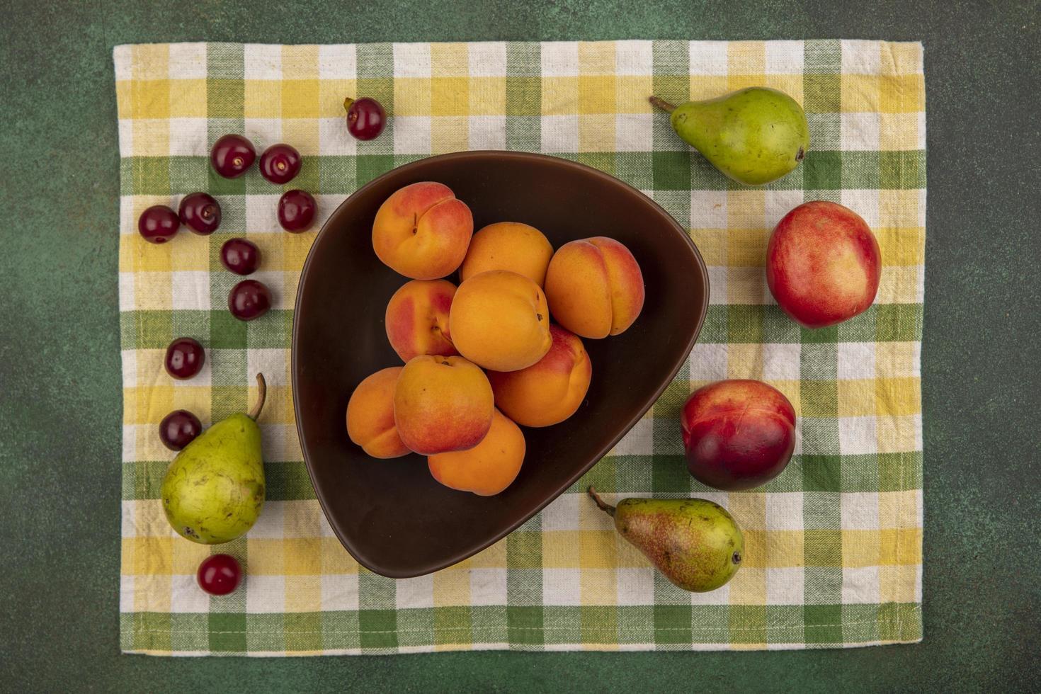 verschiedene Früchte auf kariertem Stoff auf grünem Hintergrund foto