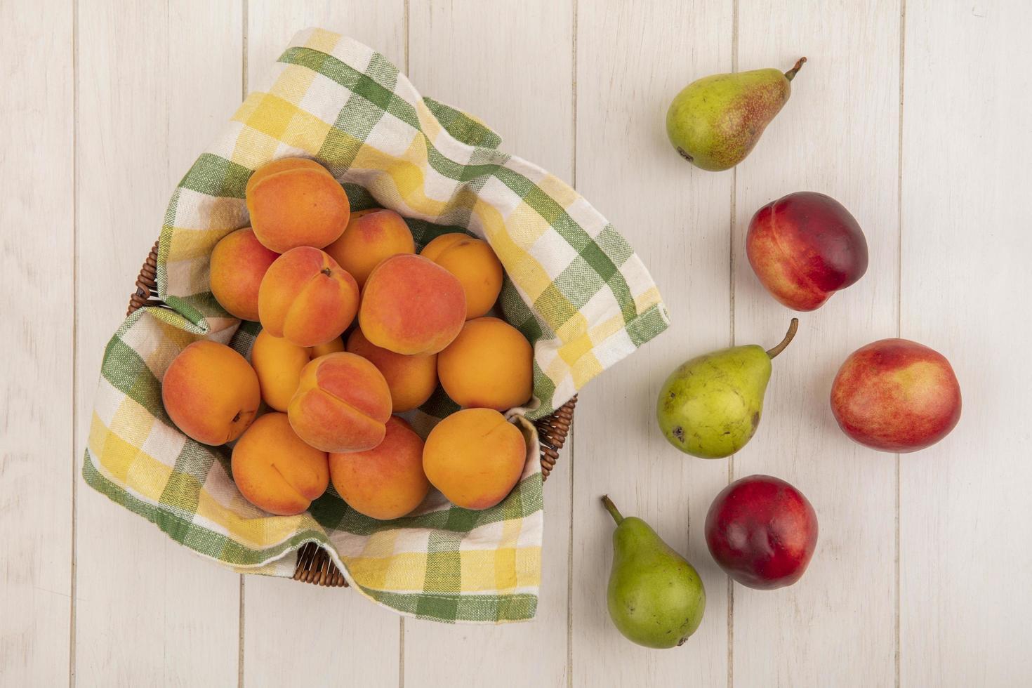 frisches Obst in einem Korb auf hölzernem Hintergrund foto