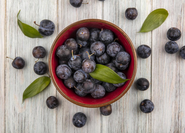 dunkle Beeren in einer Schüssel auf hölzernem Hintergrund foto