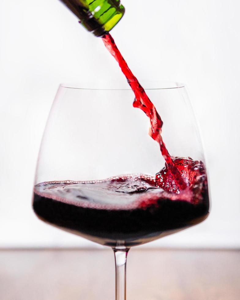 Rotwein fließt ins Glas foto