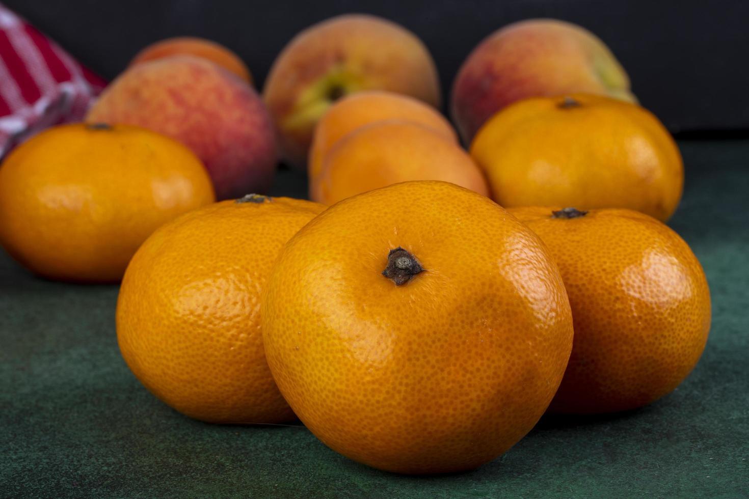 Vorderansicht von Mandarinen mit Pfirsichen auf einem grünen Hintergrund foto