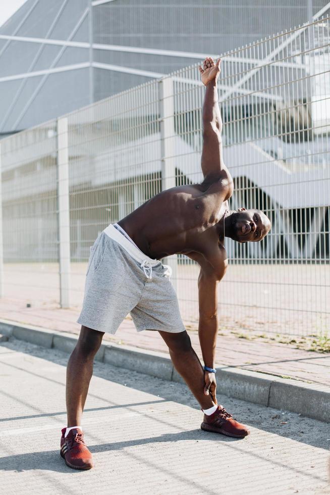 Der hübsche Afroamerikaner streckt sich vor einem Training im Freien foto