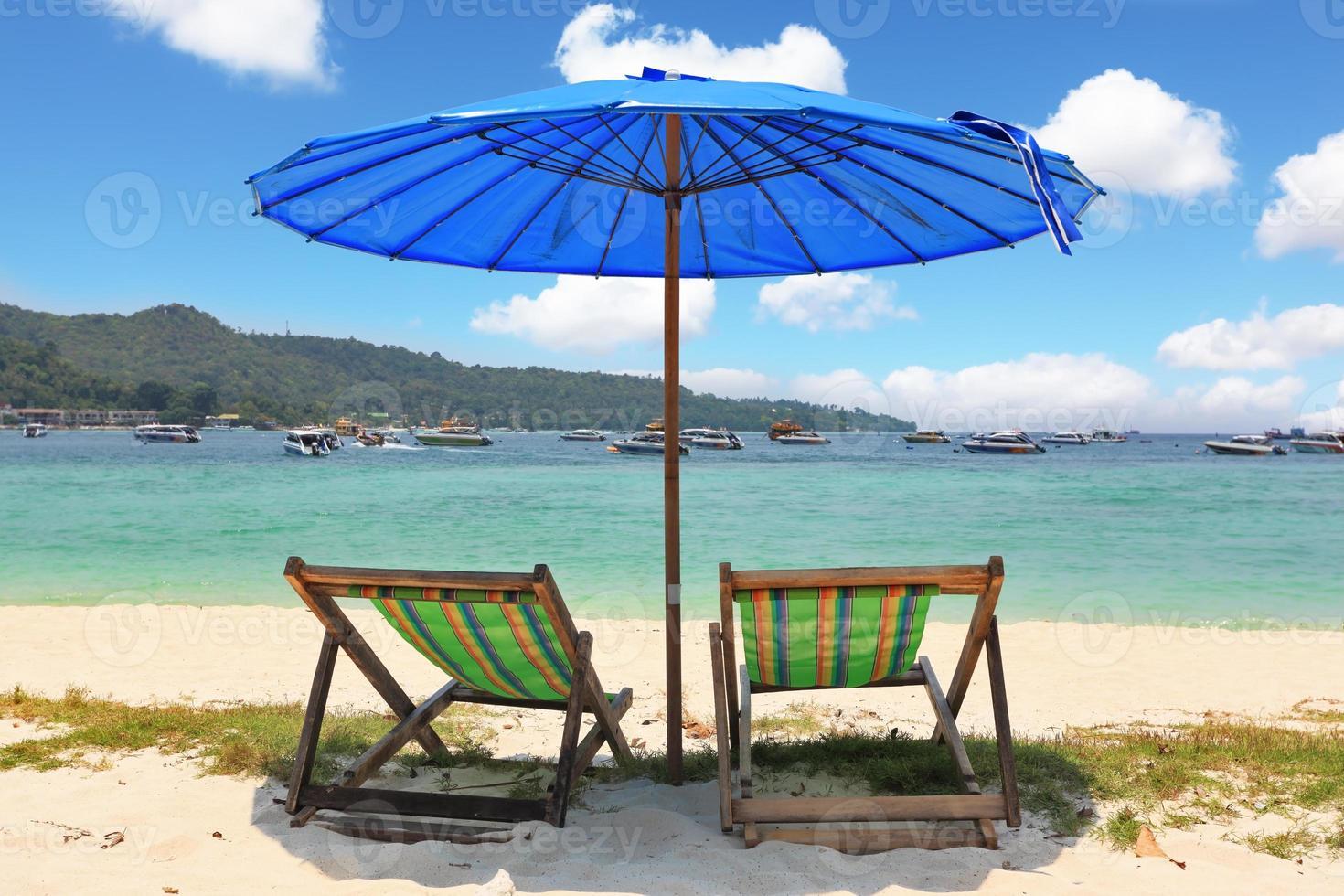 blauer Sonnenschirm und gestreifte Chaiselongues foto