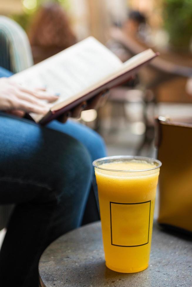 Frau, die ein Buch mit Orangencocktail im Café liest foto