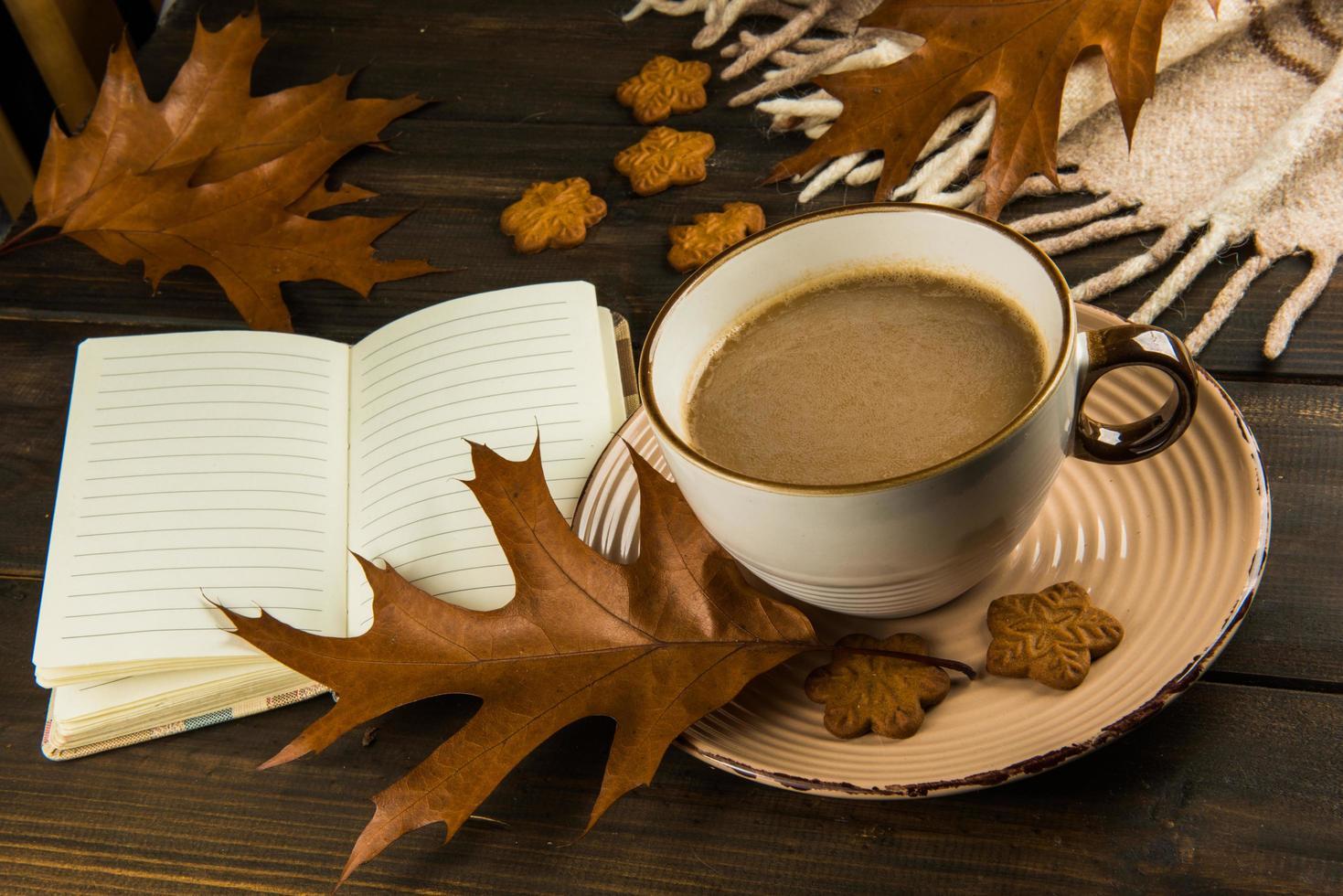 Tasse Kaffee mit Blättern, Notizbuch und Keksen foto