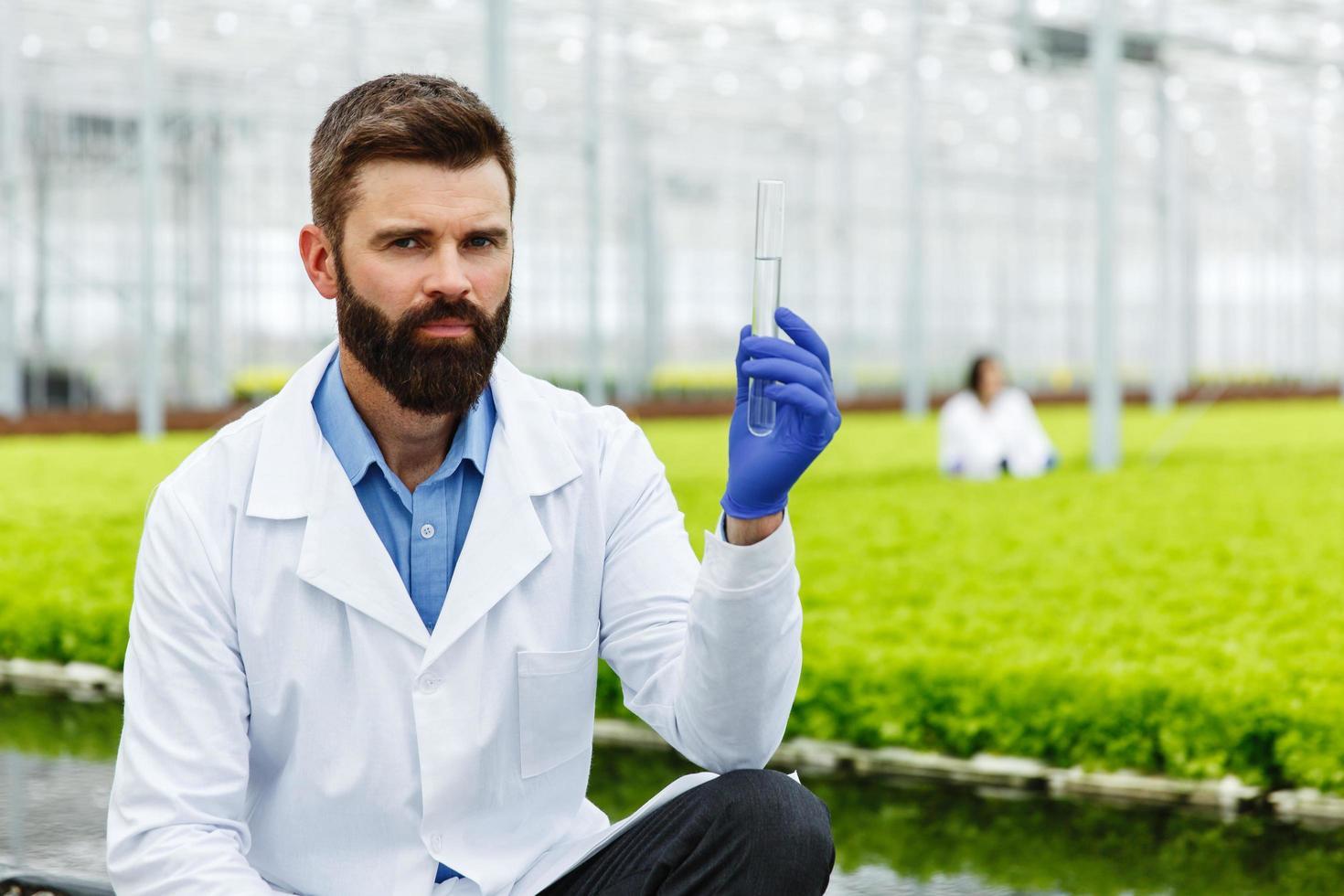 Nachdenklicher Mann Forscher hält eine Glasröhre mit Probe foto