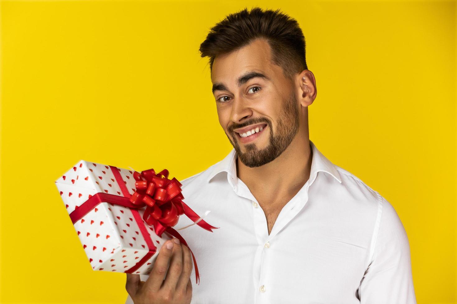 lächelnder Kerl, der eine Geschenkbox hält foto