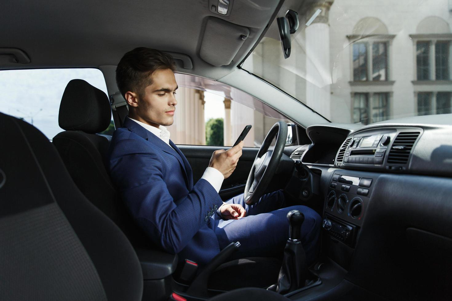 Mann überprüft sein Telefon im Auto foto