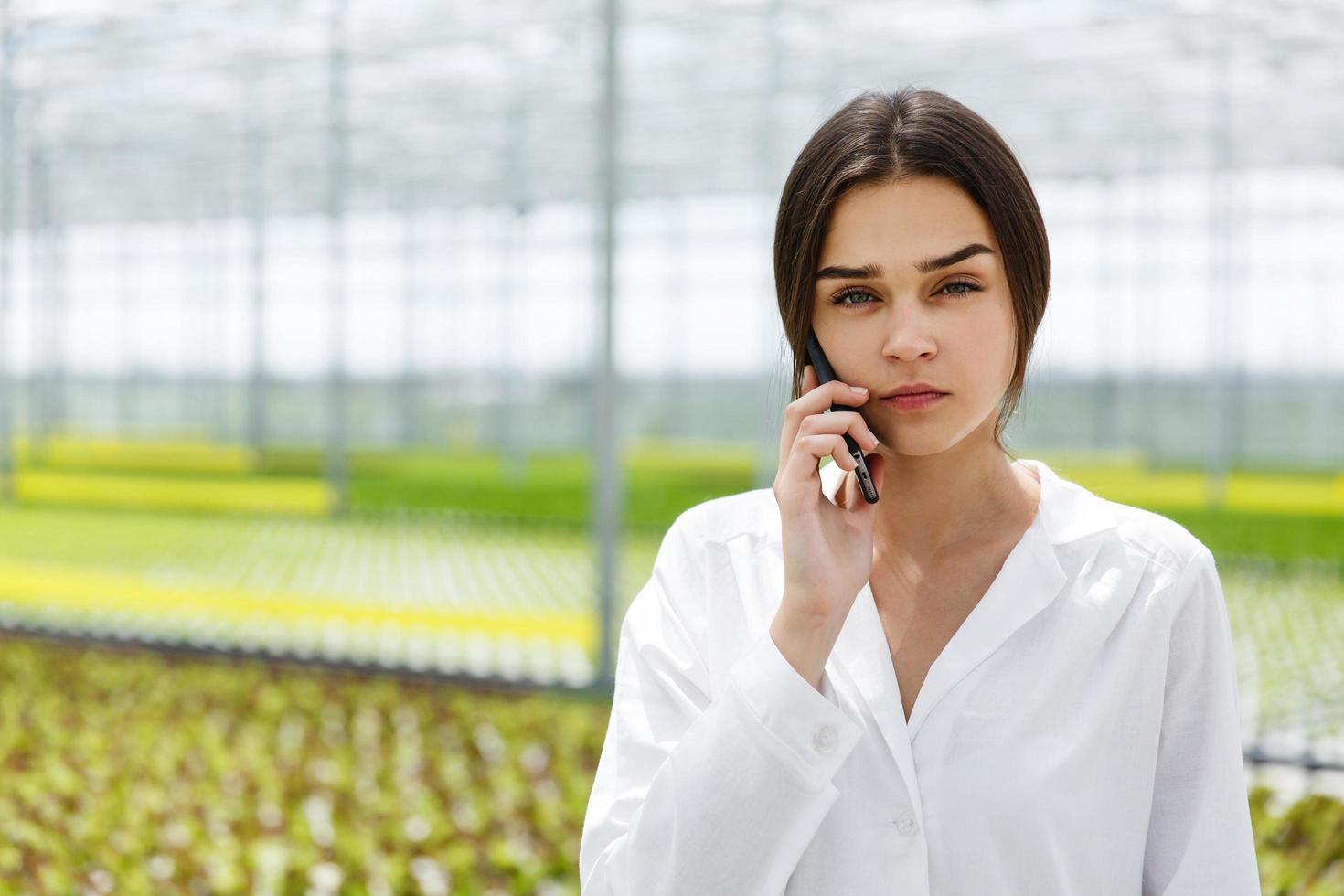Forscher telefonieren um ein Gewächshaus herum foto